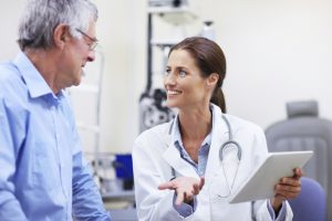 female physician and happy male patient reviewing medical office technology